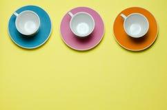 Tazas en los platillos coloridos Fotografía de archivo libre de regalías