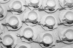 Tazas en los platillos con las cucharas Fotos de archivo