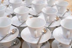 Tazas en los platillos con las cucharillas Imagen de archivo libre de regalías