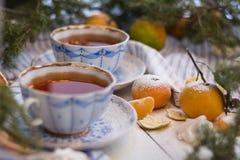Tazas hermosas de la porcelana en un fondo de madera blanco adornado para la Navidad con el azúcar en polvo y las mandarinas E Imagenes de archivo