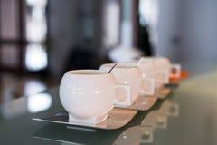 Tazas modernas de la porcelana blanca con los platillos y spo del acero inoxidable Imagenes de archivo