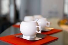 Tazas modernas de la porcelana con los platillos y las cucharas del acero inoxidable encendido Foto de archivo