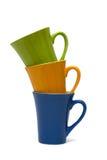 Tazas multicoloras aisladas en el fondo blanco fotografía de archivo libre de regalías