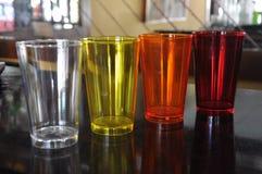 Tazas plásticas coloridas en una barra Fotos de archivo libres de regalías