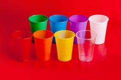 Tazas plásticas coloreadas en fondo rojo Fotografía de archivo libre de regalías