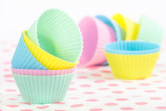 Tazas que cuecen de la magdalena en colores en colores pastel Foto de archivo