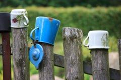 Tazas que cuelgan en la cerca Imagen de archivo