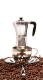 Tazas que se reclinan sobre los granos de café con el percolador Fotografía de archivo