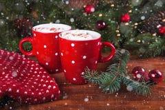 Tazas rojas con el chocolate caliente y las melcochas Fotografía de archivo libre de regalías
