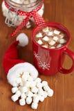 Tazas rojas con el chocolate caliente y las melcochas Imágenes de archivo libres de regalías