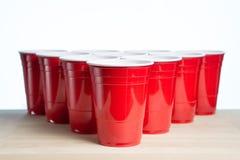 Tazas rojas del partido en la tabla de madera para el torneo del pong de la cerveza aislada en blanco Envases del alcohol de la u Imagenes de archivo