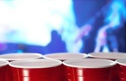 Tazas rojas plásticas del partido en fila en un club nocturno por completo de la gente que baila en la sala de baile en el fondo Fotografía de archivo