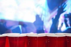 Tazas rojas plásticas del partido en fila en un club nocturno por completo de la gente que baila en la sala de baile en el fondo Foto de archivo libre de regalías