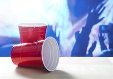 2 tazas rojas plásticas del partido en una tabla Uno en su lado Imágenes de archivo libres de regalías
