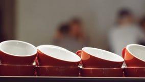 Tazas rojas vacías para el café express y para la situación del café y de la leche y calentar en la superficie de la máquina del  almacen de metraje de vídeo