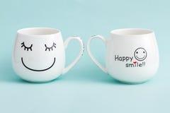 Tazas sonrientes del café con leche en fondo verde Fotografía de archivo
