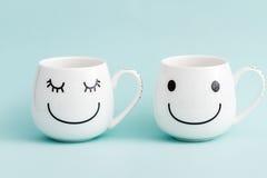 Tazas sonrientes del café con leche en fondo verde Imagenes de archivo