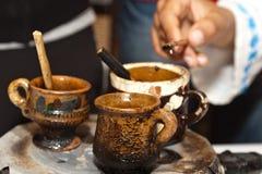 Tazas tradicionales rumanas de la arcilla con la cera caliente imagen de archivo libre de regalías