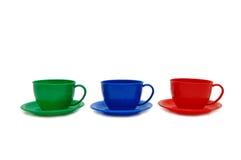 Tazas tricolores - juguetes en un fondo blanco Foto de archivo