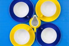 Tazas vacías del arreglo de la simetría de té en la tabla de madera azul imagen de archivo libre de regalías