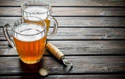 Tazas y abrelatas de cerveza imagenes de archivo