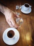 Tazas y agua de café en la tabla de madera Imagen de archivo libre de regalías