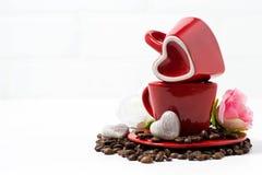 tazas y caramelos de chocolate rojos bajo la forma de corazón en blanco Imagen de archivo