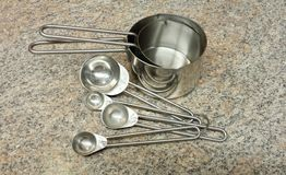 Tazas y cucharas de acero de medición Foto de archivo libre de regalías