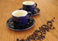 Tazas y habas de café Foto de archivo