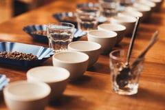 Tazas y habas de café en la tabla lista para una prueba foto de archivo