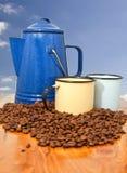 Tazas y habas de la caldera del café con el fondo azul Fotos de archivo