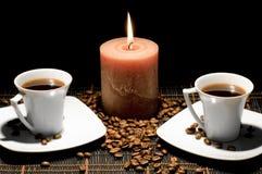 Tazas y la vela en el fondo negro. Imagen de archivo
