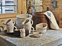 Tazas y placa en el worktop en la cocina Fotos de archivo libres de regalías
