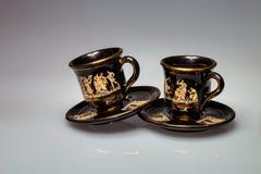 Tazas y platillos con los adornos griegos Fotos de archivo
