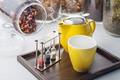 Tazas y sistema de la tetera con los relojes y té flojo en un envase en el fondo blanco, producto para el salón de té en la placa Foto de archivo libre de regalías