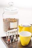 Tazas y sistema de la tetera con los relojes y té flojo en un envase en el fondo blanco, producto para el salón de té en la placa Imágenes de archivo libres de regalías