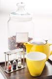 Tazas y sistema de la tetera con los relojes y té flojo en un envase en el fondo blanco, producto para el salón de té en la placa Imagen de archivo libre de regalías