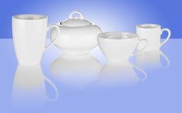 Tazas y tazón de fuente de azúcar blancos en fondo azul Imagen de archivo
