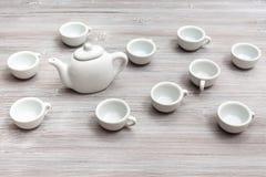 Tazas y tetera de cerámica blancas en la tabla marrón gris Imagenes de archivo