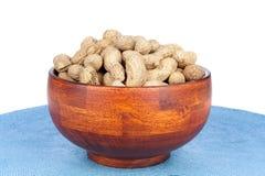 Tazón de fuente de cacahuetes en un fondo blanco Fotografía de archivo libre de regalías