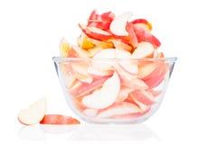 Tazón de fuente de cristal de manzanas cortadas aisladas en blanco Imagen de archivo