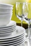 Tazones de fuente blancos llanos de las placas y vidrios de vino cristalinos Fotos de archivo