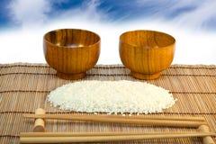 Tazones de fuente y arroz en la estera de madera con los palillos Foto de archivo libre de regalías