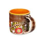 Tazza arancio con gli ornamenti floreali etnici su fondo bianco Fotografia Stock