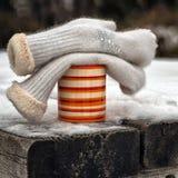 Tazza arancio con i guanti bianchi alla tavola di legno Immagini Stock Libere da Diritti