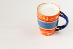 Tazza arancio di latte e di caffè su fondo di legno bianco Immagine Stock Libera da Diritti