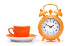 tazza arancio e sveglia isolate Immagine Stock