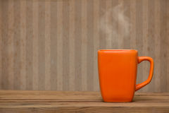 Tazza arancio su una tavola di legno sopra la carta da parati di lerciume Fotografie Stock Libere da Diritti