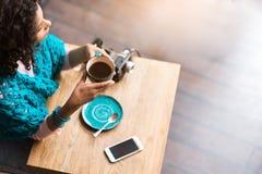 Tazza bevente della giovane donna pensierosa di caffè caldo Fotografia Stock