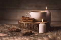 Tazza bianca con caffè, le candele, la cannella, la pelliccia ed i coni fotografia stock